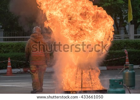 the fireman in set fire uniform. He stood with his back to the fire bigger. very hot. The massive fire. background - stock photo