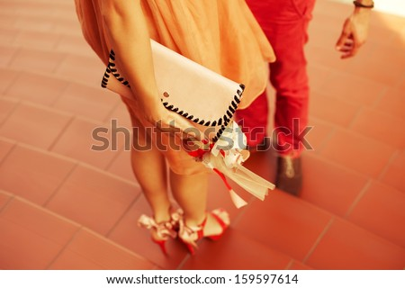 The first date concept. Young couple of hipsters wearing trendy clothing and shoes standing together on stairs. Sunny day. Copy-space. Outdoor shot - stock photo
