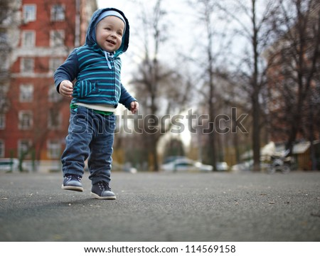 The first independent steps of the kid. Natural colors, shallow dof. - stock photo