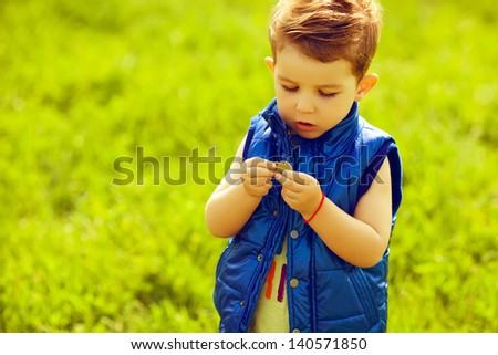 The first investment concept. Portrait of a stylish baby boy with ginger (red) hair holding coins in the park. Hipster style. Sunny weather. Copy-space. Outdoor shot - stock photo