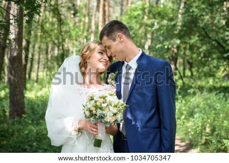 The first kiss of a newly formed wedding family. Beautiful bride and handsome man groom kissing in a forest