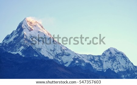 The first  lighting from the sunrise of the day touching the summit of the snow mountain with clear weather, blue sky background