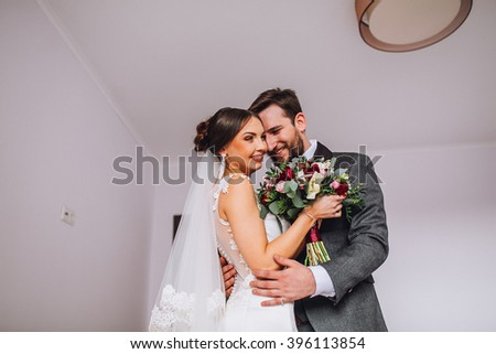 The first meeting of the bride and groom on the wedding day. Emotions newlyweds before the wedding ceremony. Bride and groom look at each other, hugging and kissing. - stock photo