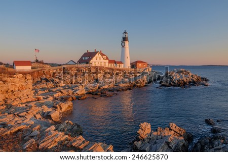 The first rays of sunrise hits the Maine Coast turning the Rocks and buildings at the Portland Head Lighthouse orange - stock photo
