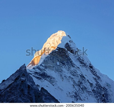 The first rays of the morning sun on the Ama Dablam (6814 m), view from the Chhukhung Ri - Everest region, Nepal - stock photo