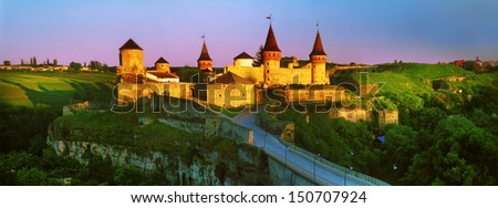 The first rays of the sun fall on the ancient walls of the fortress in the town of Kamenetz-Podolsk - stock photo