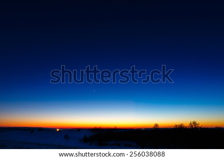 The first stars in the background of a bright sunset. - stock photo