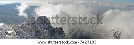 The first storm of the winter on the top of the Sandia Mountains coats the trees, plants and cliffs with ice and snow as the clouds hover around the mountaintops - true panorama - stock photo
