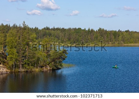 the fisherman in the rubber boat on the lake in the summer