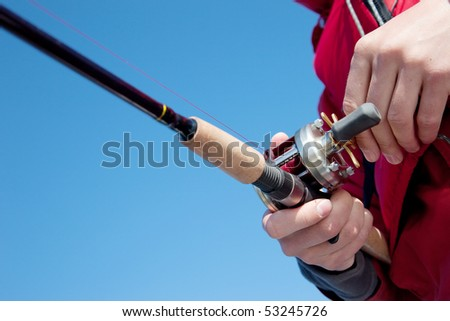 The fisherman with a baitcasting reel - stock photo