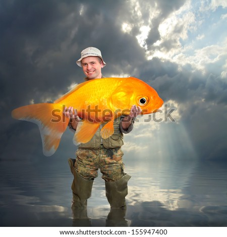 The fisherman with big Goldfish. Success concept.  - stock photo