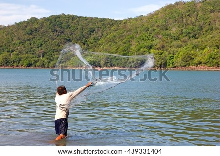 The fishermen were netting to catch fish in the river - stock photo