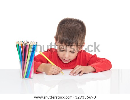 The five-year-old boy sits at a white table and draws pencils, isolated on a white background