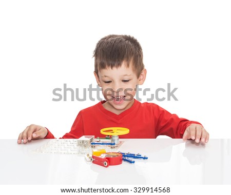 The five-year-old boy sits at a white table and plays an electronic designer (meccano, constructor) starts the propeller,  isolated on a white background - stock photo