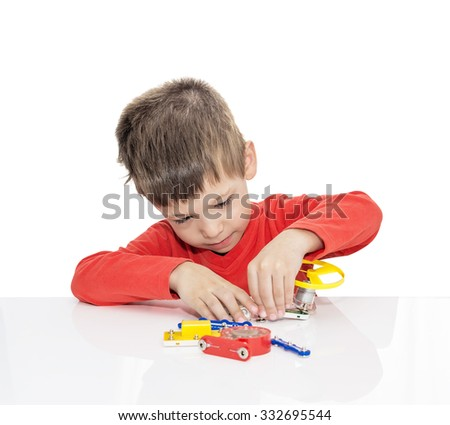 The five-year-old boy sits at a white table and plays an electronic designer (meccano, constructor),  isolated on a white background