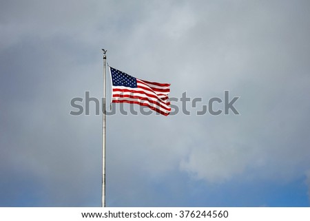 the flag of American with the cloudy sky
