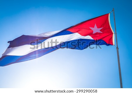 The flag of Cuba waving in the wind against a blue sky - stock photo