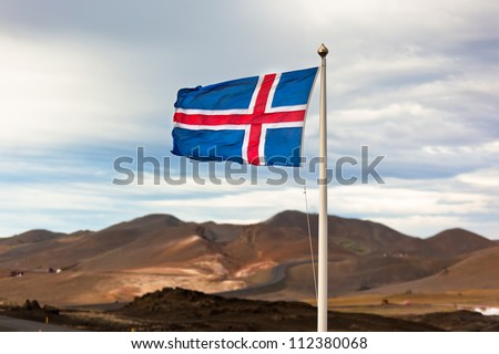 The flag of Iceland waving in the windon a background of a stormy sky - stock photo