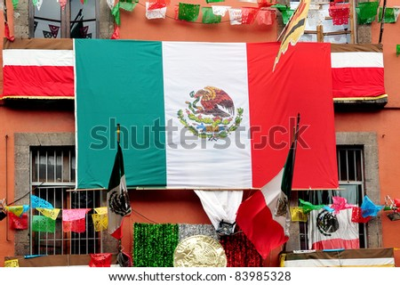 The flag of the United Mexican States hangs outside a house. - stock photo