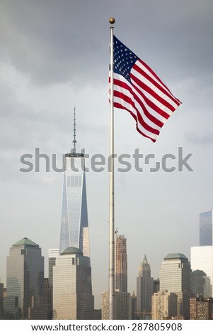 the flag of the United States in front of the skyscrapers in New York - stock photo