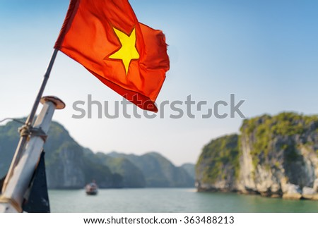 The flag of Vietnam (red flag with a gold star) fluttering on ship in the Halong Bay at the Gulf of Tonkin of the South China Sea, Vietnam. Karst towers-isles and blue sky are visible in background.