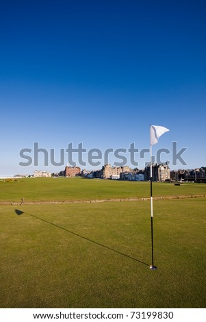 The flag on the first hole of the famous Old Course links in St Andrews on a clear sunny afternoon. - stock photo