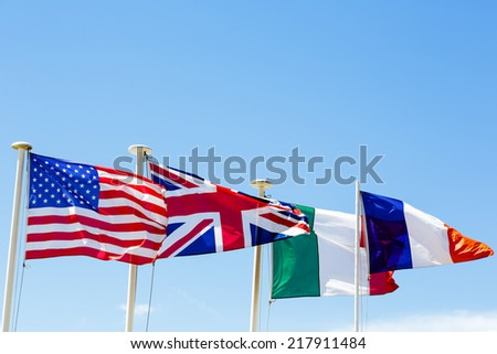 The flags of four countries against a blue sky - stock photo