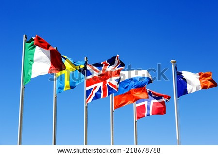 The flags of six countries against a blue sky - stock photo