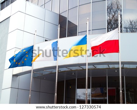 The Flags of the European Union, Ukraine, Poland, and other on office business building background - stock photo