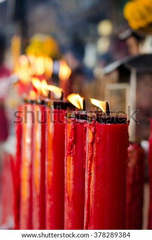 The flame on red candle at the Chinese temple.