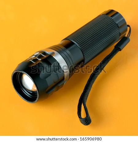 The flashlight on a orange background - stock photo