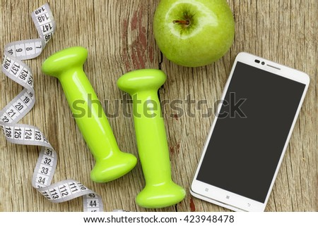 The flat position, White smart-phone, ripe green apple, dumbbells and measuring tape on a gray wooden background. Concept: the fashion for a healthy lifestyle - stock photo