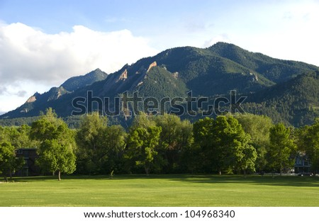 The Flatirons Mountains above Boulder, Colorado, as seen from North Boulder Park on a quiet summer day - stock photo