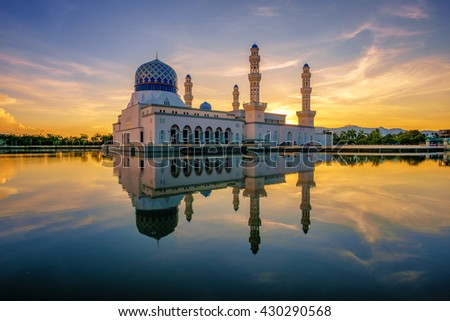The floating City Mosque, also known as Likas Mosque at Kota Kinabalu, Sabah, Malaysia during sunrise. The calm lagoon surface reflects the color of the sky. - stock photo