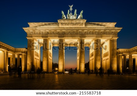 The floodlit Brandenburg Gate in Berlin with a few fleeting shadows of anonymous Berliner's - Symbol of Germany. - stock photo