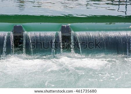 The flow of water through the weir in the side stream of the river Reuss forms a small waterfall in Lucerne in Switzerland
