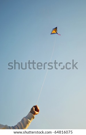 The Flying color kite and hand - stock photo