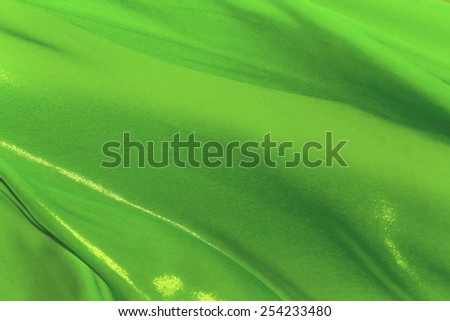 The folds of green silk fabric fluttering in the wind - stock photo