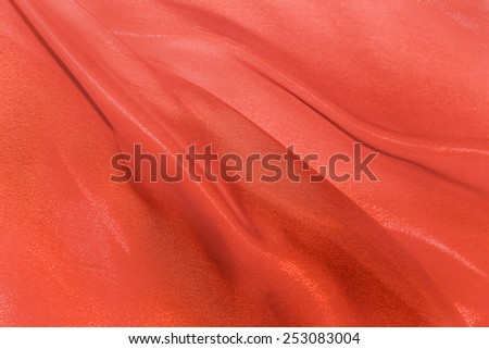 The folds of red silk fabric fluttering in the wind - stock photo