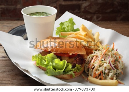 The food with soup, burger and salad on a tray with white paper - stock photo