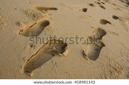 The foot step on the beach sand in a day time