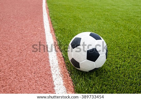 The football is on the artificial grass soccer field in the stadium. - stock photo