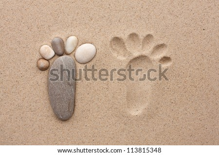 The footprint made up of stones on a sandy background - stock photo