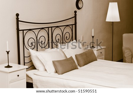 The forged headboard of bed with pillows and a white coverlet. Candles in a room interior, a bedroom - stock photo