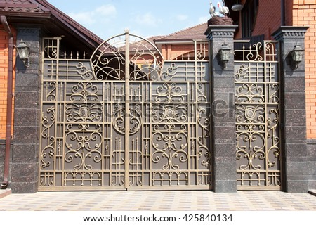 the forged metal gate with a nest of storks - stock photo