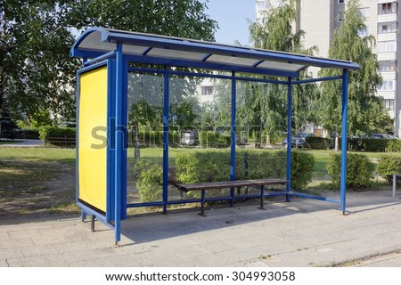 The forgotten empty mass production bus-stop in the sleepy summer small city. Hot sunny day urban landscape.  - stock photo