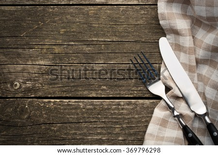 the fork and knife on old wooden table - stock photo