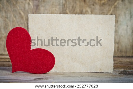 the form for a card on wooden background .   handmade heart from red felt is  in the left corner of the form - stock photo
