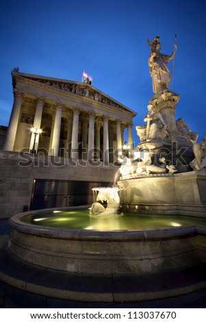 The fountain of Athena and the grand Austrian Parliament in Vienna, at twilight - stock photo