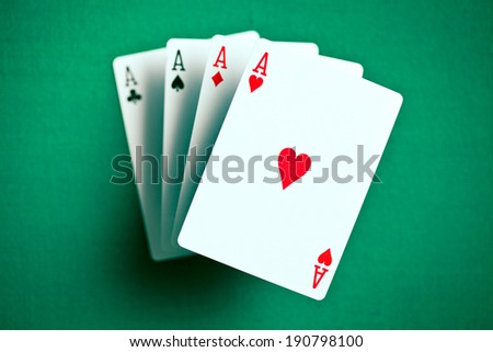 the four aces on green casino table - stock photo